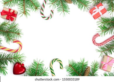 Christmas Frame of Fir tree branch with candy canes and boxes isolated on white background with copy space for your text