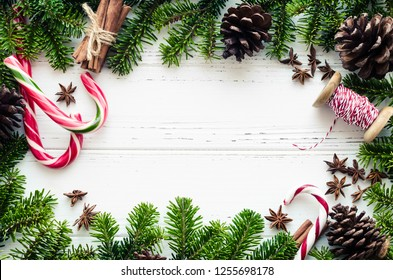 Christmas frame from fir tree branches, natural decorations and candy canes on white background with space for text. Merry Christmas and Happy New Year. Xmas concept. Top view. Flat lay. Copy space.