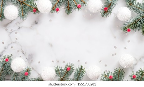 Christmas frame with fir tree branches, white balls, red berries and confetti on marble background. Flat lay, top view, overhead