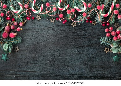 Christmas frame with fir twigs, red berries and candy canes on textured dark blue board with copy-space