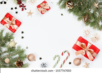 Christmas frame flat lay with pine, red presents, golden elements, candy canes, confetti. Christmas template on white background. Golden baubles, red gift boxes, pine. Christmas background, copy space