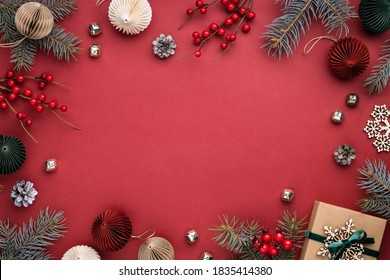 Christmas frame with gift box, paper decorations, spruce branches and berries on red background. Holiday border in earth colours.