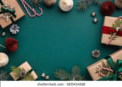 Christmas frame with gift boxes, paper decorations, jingle bells and spruce branches on turquoise background. Holiday background in earth colours.