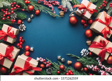 Christmas frame with gifts, evergreen branches and red decorations on dark blue background.
