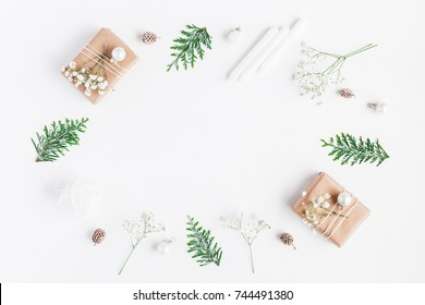Christmas frame. Christmas gifts, pine cones, gypsophila flowers, thuja branches on white background. Flat lay, top view, copy space