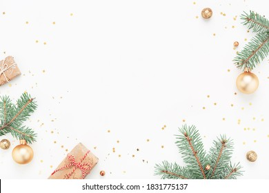Christmas frame of green branches, gifts, gold decorations on white background. Holiday Copy space, flat lay.