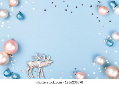 Christmas frame made of Christmas balls and silver confetti with figurine of reindeer on blue background. Minimal New Year card, top view.