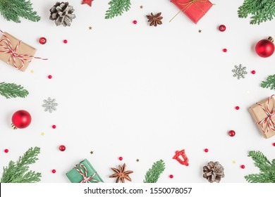 Christmas frame made of fir branches, gift boxes, red holiday decorations and pine cones on white background. Christmas or Happy New Year concept. Flat lay. top view with copy space