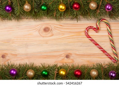 Christmas frame made of fir branches decorated with balls and candy cane on a light wooden background