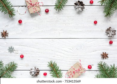 Christmas frame made of fir branches, red berries, gift boxes and pine cones on white wooden table. Christmas background. Flat lay. top view with copy space