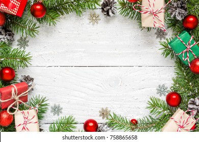 Christmas frame made of fir branches, festive decorations, gift boxes and pine cones on white wooden table. Christmas background. Flat lay. top view with copy space