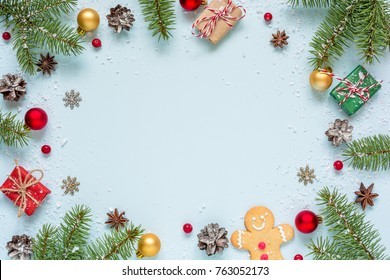 Christmas frame made of fir branches, red berries, gift boxes and pine cones on blue background. Christmas background. Flat lay. top view with copy space