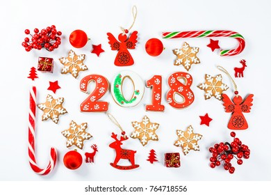 Christmas frame made of red toys and New Year decorations with gingerbread cookies 2018 on white background. Flat lay, top view, copy space. Merry christmas card