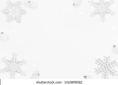 Christmas frame made of snowflakes and balls on white background with copy space. Christmas concept. Flat lay, top view