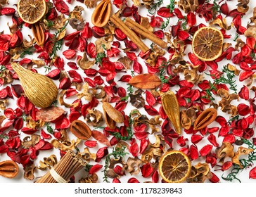 Christmas frame - postcard from scattered spruce twigs, red dry petals of fruit tree, golden fruits, cinnamon sticks with place for your text on a white background. New Year pattern