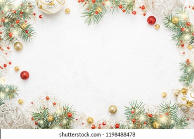 Christmas frame of spruce, red & gold christmas decorations on white background. Copy space. New Year lights. Flat lay.