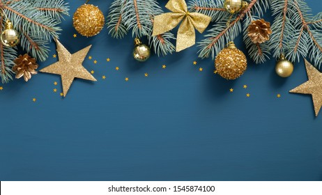 Christmas frame top border made of fir tree branches, golden decorative stars, balls over blue background. Flat lay, top view. Xmas banner mockup with copy space