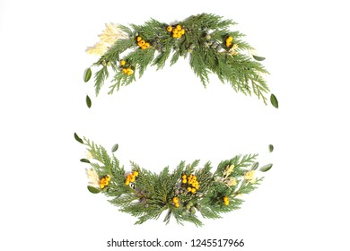 Christmas frame wreath with evergreen branches and red and yellow berries. Flat lay, top view.