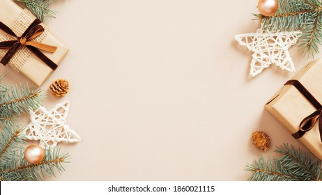 Christmas frame. Xmas tree branches decorated gift boxes, stars and balls on beige background. Flat lay, top view, copy space. Christmas banner mockup, poster template.