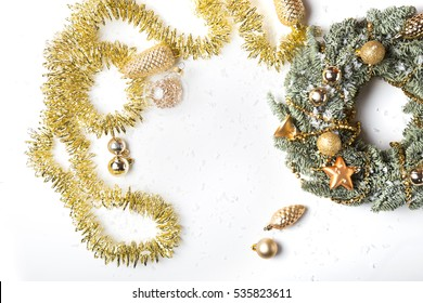Christmas fresh green and golden wreath with decorations, toys, balls and garland isolated on white background top view. Copy space for text.  New Year stylized  composition