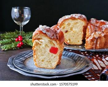 Christmas fruit bread wreath slice on the Christmas table over dark background.