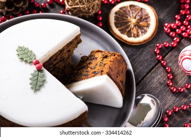 Christmas fruit cake on wooden table with festive decorations