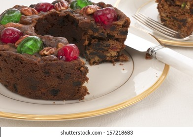 Christmas Fruit Cake with red and green cherries on top on a China Plate on a Table with a White Table Cloth