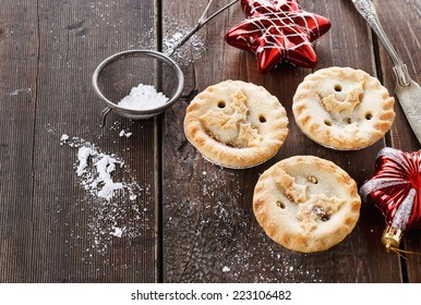 Christmas fruit mince pies and red Christmas ornaments over rustic wooden background