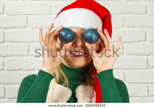 Christmas fun. woman in santa red hat holding Christmas balls in front of her eyes and smiling assign white brick wall