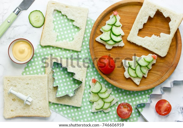 Christmas funny sandwiches with bread, cucumber slice, tomato star and sauce for kids