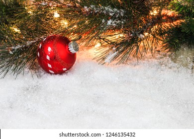 Christmas garland border with lights, red and silver ornament in white snow border; holiday background with copy space