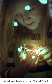 Christmas garland in the hands of a girl