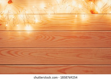 christmas garland string with led lights on top of natural wooden background