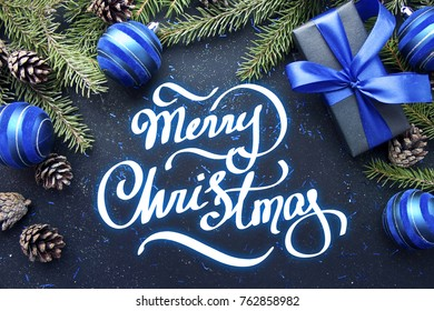 Christmas gift with blue ribbon and blue balls, tree branches and cones on dark blue background with hand lettering Merry Christmas.