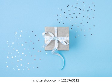 Christmas gift with blue ribbon on blue pastel background with festive decorations. Christmas background with copy space.