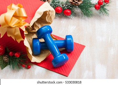 Christmas gift blue sport dumbbells in red box, Christmas tree decorations with berries and cones