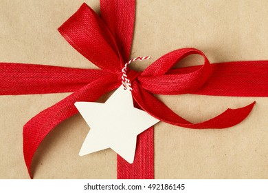 Christmas gift with bow and blank gift tag. Simple recycled wrapping paper and natural jute ribbon.