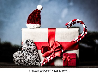 Christmas gift with bowknot and lollipop with candy on grey background