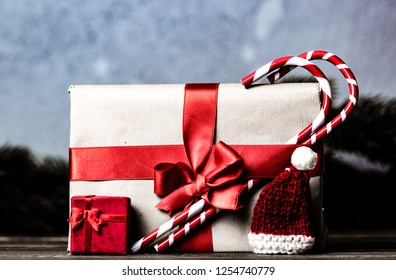 Christmas gift with bowknot and lollipop on grey background