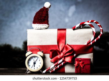 Christmas gift with bowknot and retro alarm clock with lollipop on grey background