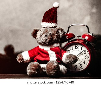 Christmas gift with bowknot and retro alarm clock with teddy bear on grey background