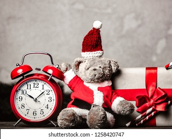 Christmas gift with bowknot and retro alarm clock near teddy bear toy on grey background