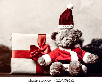 Christmas gift with bowknot and teddy bear toy on grey background