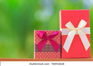 Christmas gift box against turquoise green bokeh background. gift box and red white ribbon with tag on burred background with space. Box for Valentines Christmas day and Holiday greeting card concept.