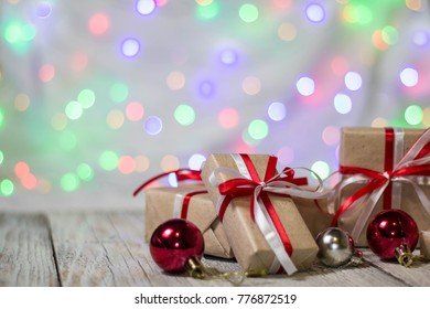 Christmas gift box with balls against bokeh background. Holiday greeting card.