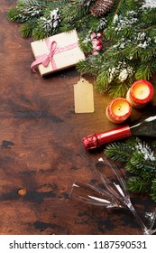 Christmas gift box, candles, champagne and fir tree branch covered by snow on wooden background. Top view xmas backdrop with space for your greetings