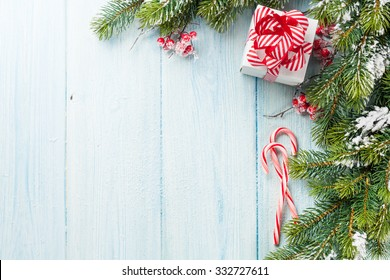 Christmas gift box, candy cane and fir tree branch on wooden table. Top view with copy space