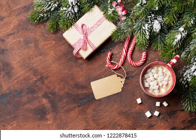 Christmas gift box, candy canes, cup of hot chocolate with marshmallow and fir tree branch covered by snow on wooden background. Top view xmas backdrop with space for your greetings