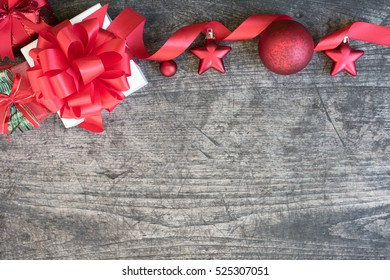 Christmas gift box decorate with red ribbon and ornament on wood background with copy space flat lay style