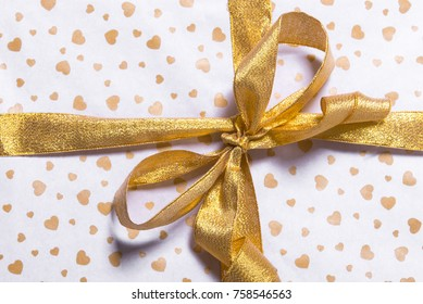 Christmas gift box with decoration on white background with a golden bow. Christmas family holiday concept. Merry Christmas and Happy Holidays. Wrap with hearts.